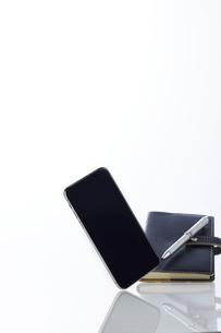 新しいスマートフォンと背景に置かれた手帳とペンの写真素材 [FYI02523910]