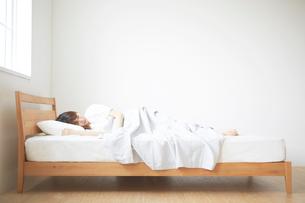 ナチュラルなベッドで眠る女性の写真素材 [FYI02523935]