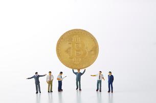 ビットコインを持ち上げるミニチュアのサラリーマンの写真素材 [FYI02523949]