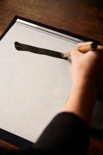 机で書道をする女性の手の写真素材 [FYI02523965]