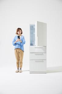 スマートフォンを持った女性と冷蔵庫の写真素材 [FYI02524037]