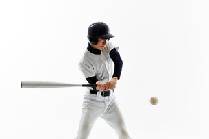バットを振る野球のユニフォームを着た男性の写真素材 [FYI02524081]