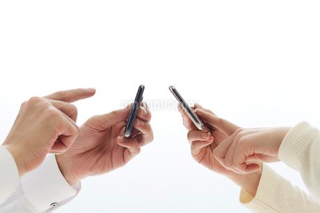 新しいスマートフォンを操作する二人の手の写真素材 [FYI02524134]