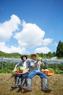 畑の前の土手に座る野菜を持つ男女の写真素材 [FYI02524172]