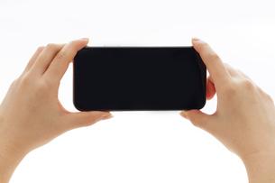 新しいスマートフォンを両手で横向きに持つ人の写真素材 [FYI02524200]