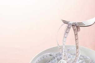 白い皿の上に乗せられたメジャーをフォークですくう様子の写真素材 [FYI02524233]