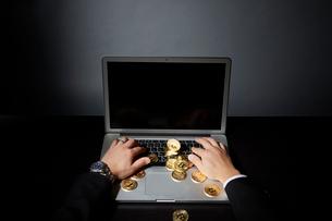 パソコンでビットコインのビジネスをするスーツを着た男性の写真素材 [FYI02524250]