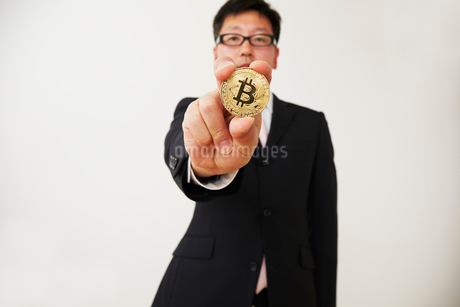 ビットコインを持ったスーツを着た男性の写真素材 [FYI02524297]