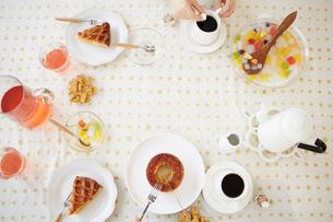 お菓子が並べられたテーブルとコーヒーを飲む女性の写真素材 [FYI02524308]