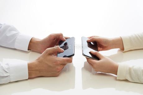 新しいスマートフォンでゲームをする二人の手の写真素材 [FYI02524322]