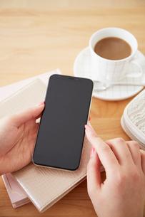 テーブルの上でスマートフォンを持つ女性の写真素材 [FYI02524366]