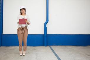 ヘルメットを被り書類を持ちながら点検をする女性の写真素材 [FYI02524406]