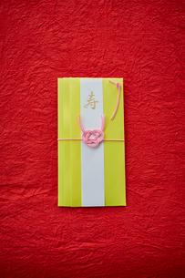 赤い天板の上に置かれた黄色いご祝儀袋の写真素材 [FYI02524410]