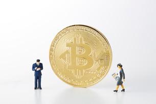 ビットコインとミニチュアのサラリーマンとOLの写真素材 [FYI02524422]