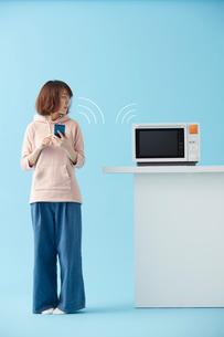 スマートフォンで電子レンジを操作する女性の写真素材 [FYI02524439]