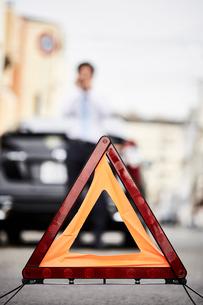 三角表示板と電話をかける男性の写真素材 [FYI02524449]