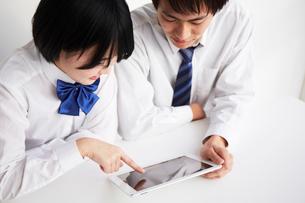 机の上でタブレットを見る男子高生と女子高生の写真素材 [FYI02524537]