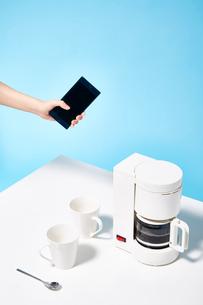 スマートフォンでコーヒーメーカーを操作するの写真素材 [FYI02524544]