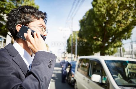 車の前で電話をかける男性の横顔の写真素材 [FYI02524566]