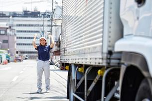 大きなトラックを誘導する働く女性の写真素材 [FYI02524707]
