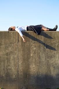 堤防に仰向けで寝る女子高生の写真素材 [FYI02524842]