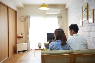 リビングでくつろぐ男女とテーブルの上に置かれたAIスピーカーの写真素材 [FYI02524881]