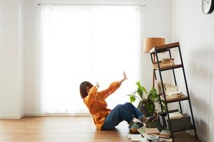 地震で倒れてきた本棚の横で驚く女性の写真素材 [FYI02524889]
