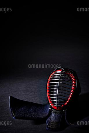 黒い背景に置かれた剣道の面の写真素材 [FYI02524899]