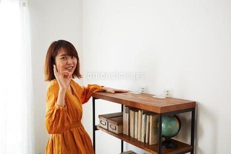 本棚に転倒防止グッズをつけている女性の写真素材 [FYI02524988]