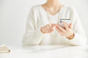 机の前に座ってスマートフォンを操作する女性の写真素材 [FYI02525032]