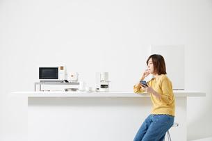 キッチンでスマートフォンを操作する女性の写真素材 [FYI02525137]