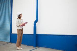 ヘルメットを被り書類を持ちながら点検をする女性の写真素材 [FYI02525205]