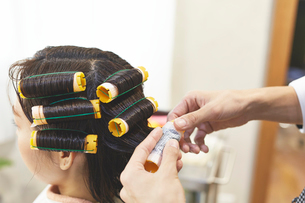 美容師にカーラーをまいてもらっている客の写真素材 [FYI02525228]