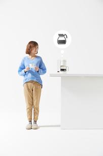 コーヒーメーカーの知らせに反応する女性の写真素材 [FYI02525295]