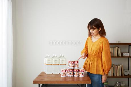 テーブルの上に置かれた保存用の水とカンパンの写真素材 [FYI02525303]