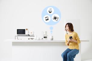 スマートスピーカーで家電を操作する女性の写真素材 [FYI02525354]