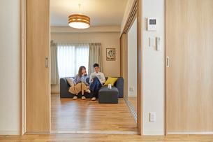 リビングでくつろぐ男女とソファに置かれたAIスピーカーの写真素材 [FYI02525738]