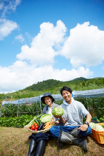 畑の前の土手に座る野菜を持つ男女の写真素材 [FYI02525773]