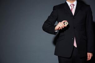 ビットコインを持ったスーツを着た男性の写真素材 [FYI02525845]