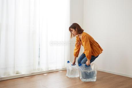 防災給水タンクに入れた水を持つ女性の写真素材 [FYI02525893]