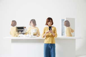 キッチンでスマートフォンを使って家電を動かす女性の写真素材 [FYI02525907]