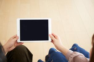 タブレット端末を一緒に持つ2人の男女の写真素材 [FYI02525909]