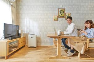 リビングルームでソファに座りタブレット端末を操作する女性とその横の男性の写真素材 [FYI02526008]
