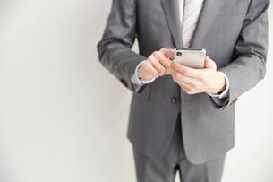 スマートフォンを操作するサラリーマンの写真素材 [FYI02526025]