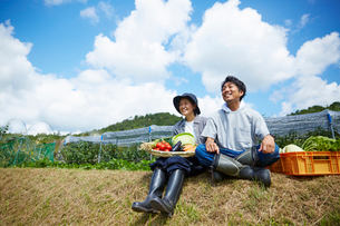 畑の前の土手に座る野菜を持つ男女の写真素材 [FYI02526113]