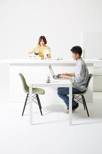 キッチンで作業する男女とテーブルに置かれたAIスピーカーの写真素材 [FYI02526205]