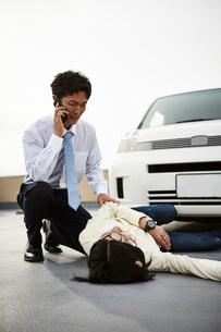 車の前に倒れている男性とその様子を見ながら電話する男性の写真素材 [FYI02528476]