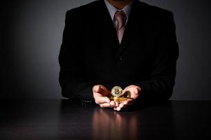 ビットコインを持ったスーツを着た男性の写真素材 [FYI02529727]