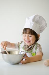 コック帽子を被って料理をするハーフの男の子の写真素材 [FYI02530070]
