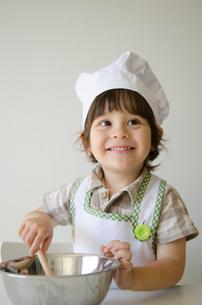 コック帽子を被って料理をするハーフの男の子の写真素材 [FYI02530174]